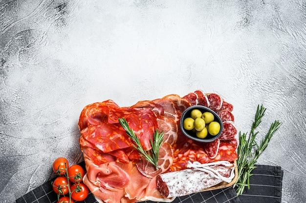 Ассорти из испанского холодного мяса. чоризо, фут, поясница, хамон иберико, оливки. серая поверхность. вид сверху. копировать пространство