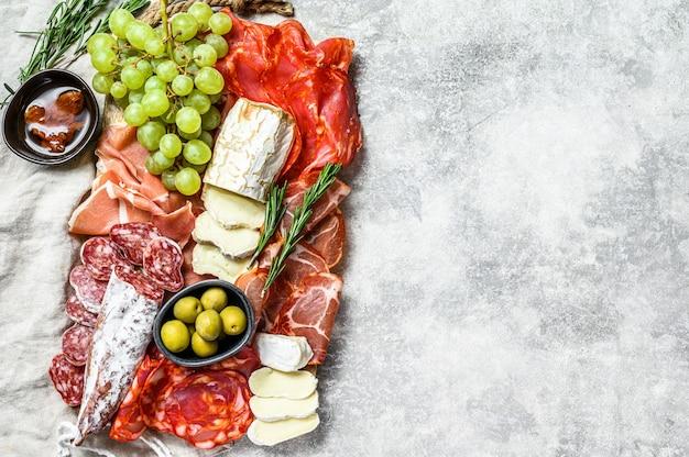 Антипасто ассорти из холодного мяса с виноградом, прошутто, ломтиками ветчины, вяленой говядиной, чоризо салями, фуэтом, камамбером и козьим сыром. серый фон. вид сверху. копировать пространство
