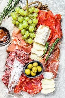 ぶどう、生ハム、スライスハム、ビーフジャーキー、チョリソサラミ、フエット、カマンベール、ヤギのチーズの冷製前菜盛り合わせ。灰色の表面。上面図