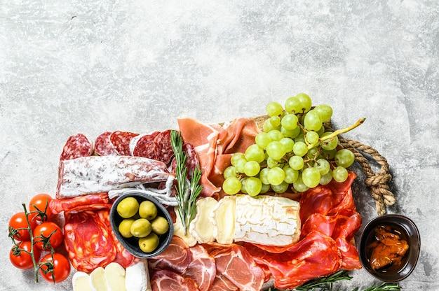 ぶどう、生ハム、スライスハム、ビーフジャーキー、チョリソサラミ、フエット、カマンベール、ヤギのチーズの冷製前菜盛り合わせ。灰色の表面。上面図。コピースペース