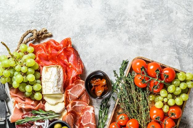 Итальянский антипасто, деревянная разделочная доска с ветчиной, ветчиной, пармой, козьим сыром и камамбером, оливками, виноградом. антипаста. серый фон вид сверху. копировать пространство