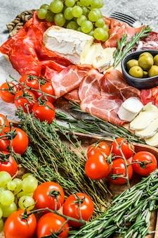 イタリアン前菜、生ハム、ハム、パルマ、ヤギ、カマンベールチーズ、オリーブ、ブドウの木製まな板。前菜。灰色の表面。上面図
