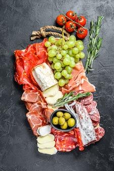 イタリアン前菜、生ハム、ハム、パルマ、ヤギ、カマンベールチーズ、オリーブ、ブドウの木製まな板。前菜。黒い表面。上面図