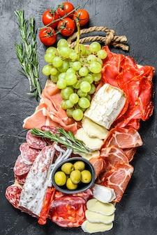 Антипасто ассорти из холодного мяса с виноградом, прошутто, ломтиками ветчины, вяленой говядиной, чоризо салями, фуэтом, камамбером и козьим сыром. черная поверхность. вид сверху