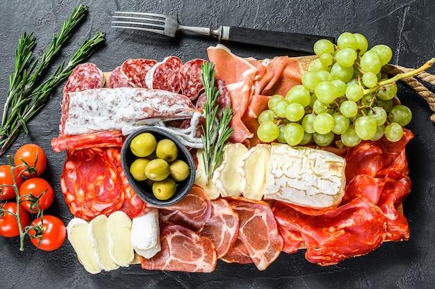 ぶどう、生ハム、スライスハム、ビーフジャーキー、チョリソサラミ、フエット、カマンベール、ヤギのチーズの冷製前菜盛り合わせ。黒い表面。上面図