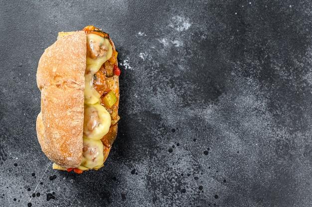 Сэндвич чиабатта с фрикадельками, сыром и томатным соусом. черный фон. вид сверху. копировать пространство