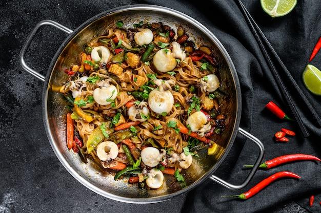 Обжарить лапшу с морепродуктами и овощами в сковороде. черная поверхность. вид сверху