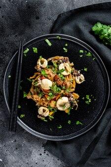 Азиатская лапша обжаривается с каракатицей и овощами. черная поверхность. вид сверху