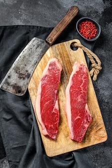 まな板の上のサーロインステーキ。有機牛肉。黒い表面。上面図