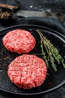 Сырые котлеты из гамбургеров, говяжий фарш. черная поверхность. вид сверху