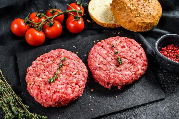 Ингредиенты для приготовления гамбургеров. фарш из говядины, булочки, помидоры, зелень и специи. черная поверхность. вид сверху