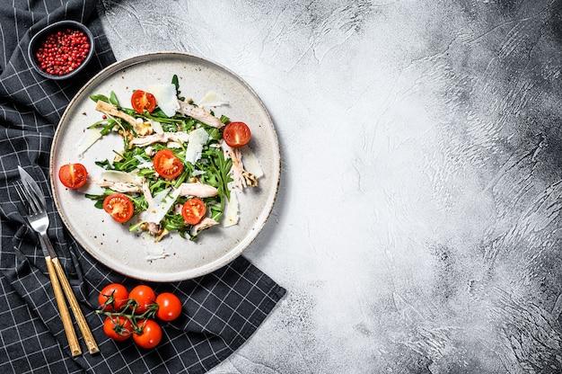 フェタチーズ、トマト、ナッツ、野菜のフレッシュチキンサラダ。健康食品のコンセプトです。灰色の表面。上面図。コピースペース