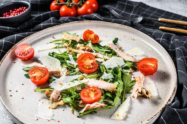 フェタチーズ、トマト、ナッツ、野菜のフレッシュチキンサラダ。健康食品のコンセプトです。灰色の表面。上面図。
