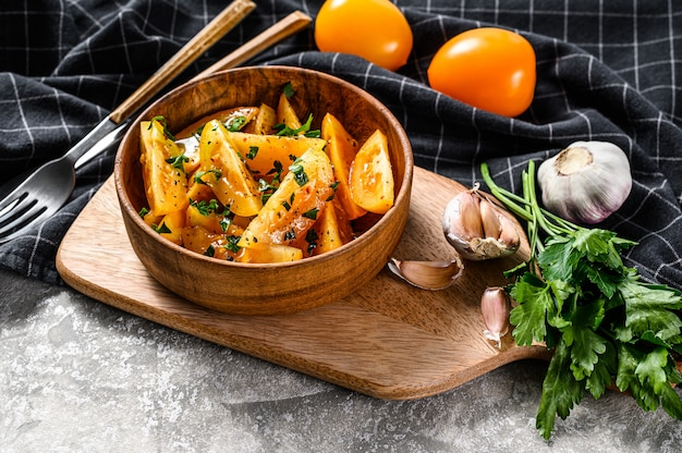 黄色いトマトとパセリのヘルシーでカラフルなサラダ。灰色の背景。上面図