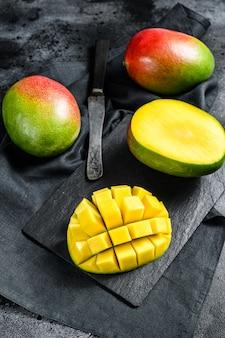 Тропический спелый плод манго. черный фон.