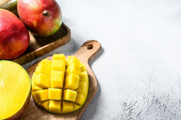 Плоды манго нарезать кубиками на разделочную доску. серый фон