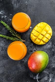Свежевыжатый сок манго в стакане. черный фон.