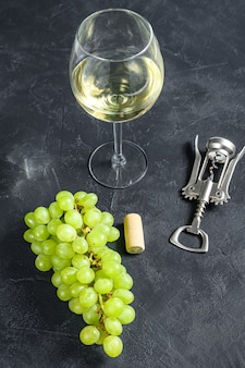 Ветка зеленого винограда, бокал, штопор и пробка. концепция виноделия. черный фон.