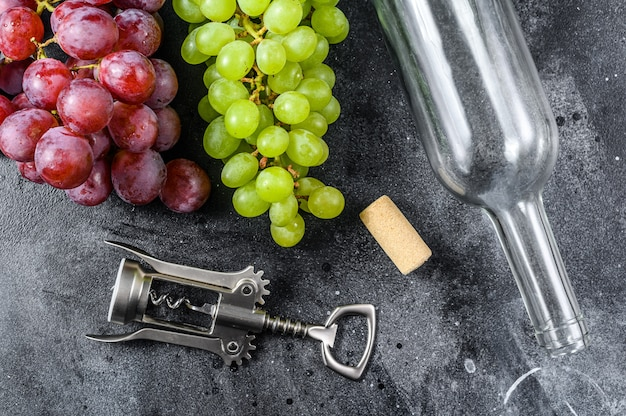 Ветка зеленого и красного винограда, бутылка, штопор и пробка. концепция виноделия. черный фон.