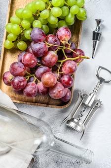Концепция домашнего виноделия. зеленый и красный виноград. винный фон.