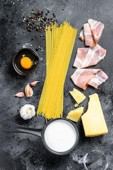 伝統的なイタリアンパスタカルボナーラの成分。ベーコン、スパゲッティ、パルメザンチーズ、ペコリーノチーズ、卵、ニンニク。黒の背景。