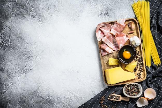 パスタカルボナーラの材料。伝統的なイタリア料理。灰色の背景。上面図。