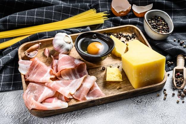 伝統的なイタリアンパスタカルボナーラの成分。ベーコン、スパゲッティ、パルメザンチーズ、ペコリーノチーズ、卵、ニンニク。