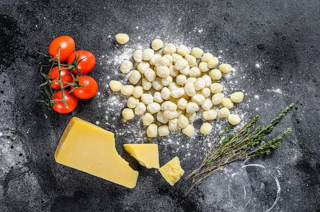 パスタを調理するための食材を使用した未調理の自家製ジャガイモのニョッキ。黒の背景。