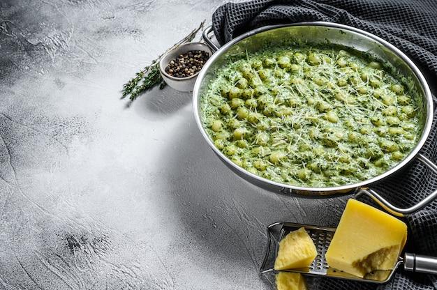 ニョッキとバジルのほうれん草ソース。イタリアンポテトペースト。灰色の背景。
