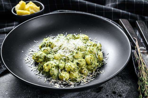 ポテトニョッキ、ペスト、パルメザンチーズ、ほうれん草。イタリアのパスタ。黒の背景。