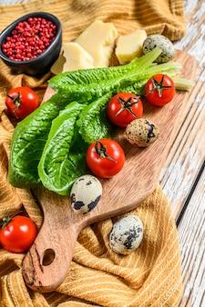 Ингредиенты салат цезарь на разделочную доску. салат ромейн, помидоры черри, яйца, пармезан, чеснок, перец. вид сверху