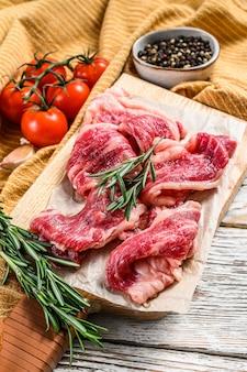牛ベーコン、まな板に霜降り肉のストリップ。白い木製の背景。上面図