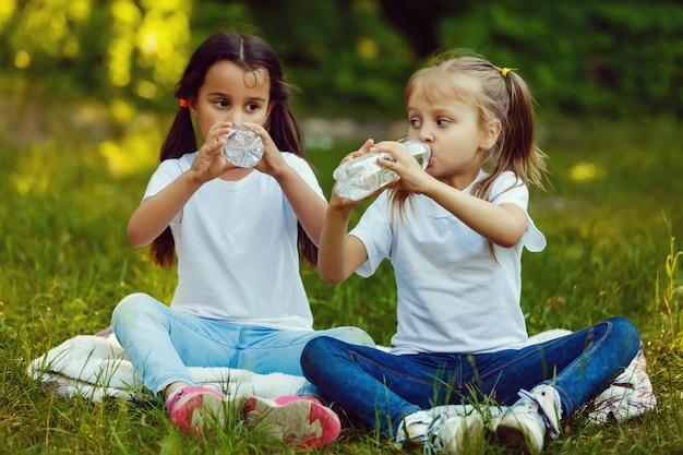 小さな女の子は公園で水のボトルを飲んでいます。