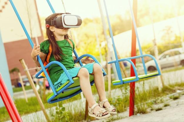バーチャルリアリティを持つ少女は、遊び場でゴーグルします。