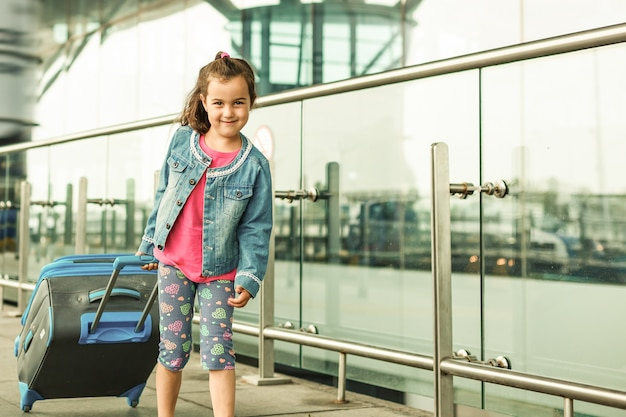 Маленькая девочка с чемоданом путешествовать в аэропорту, дети путешествуют