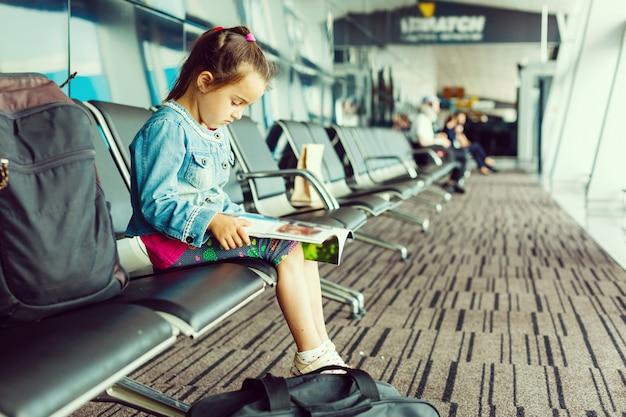 Маленькая девочка с чемоданом путешествовать в аэропорту