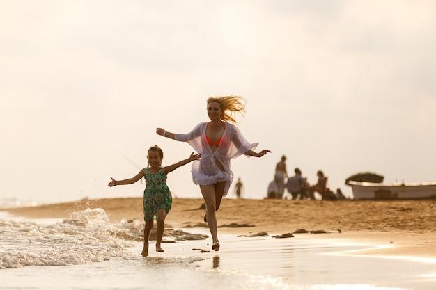 幸せな家族の母と子の娘を実行、笑って、ビーチで遊ぶ