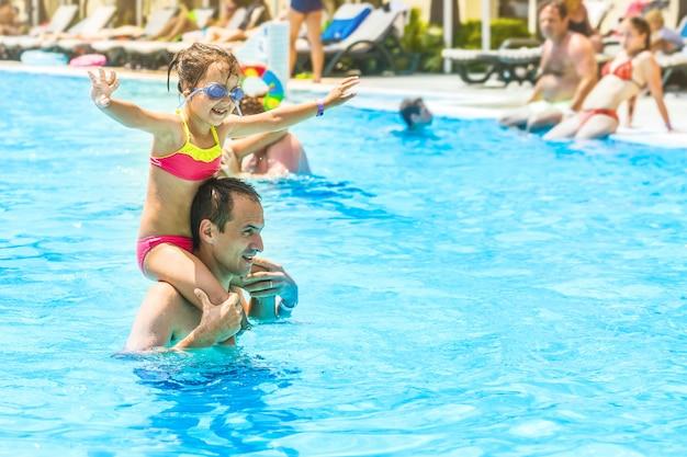 小さな女の子と屋外スイミングプールで一緒に楽しんで幸せなお父さん