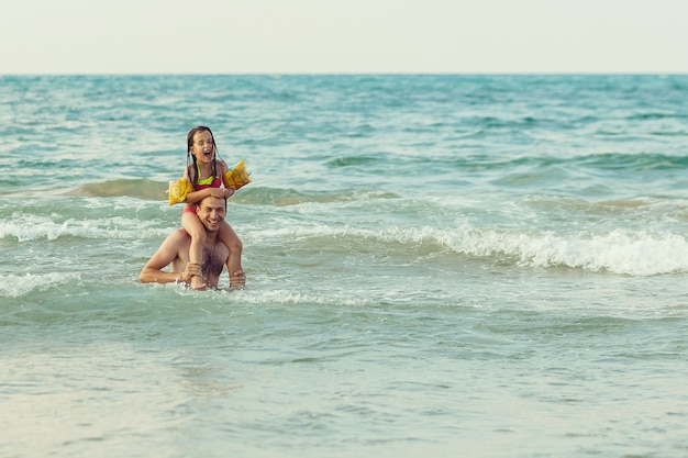 幸せな父とビーチで彼のかわいい小さな娘