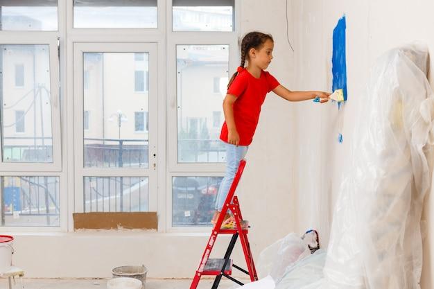 自宅の壁を塗る少女