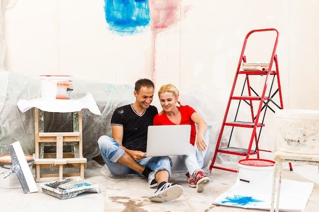 部屋の壁の絵の色を選択する若いカップル