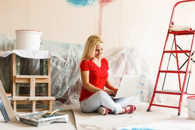部屋の壁の絵の色を選択する若い女性