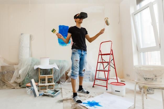 仮想現実のゴーグルで壁を塗る若い男