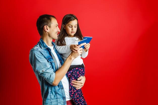 Отец и красивая дочь с паспортом на красном фоне