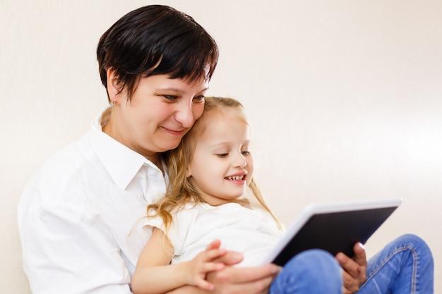 ママと娘がタブレットを使用して母と娘がタブレットコンピューターを使用して一緒に