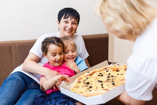 自宅のソファーに座りながらピザを食べて幸せな家族の肖像画