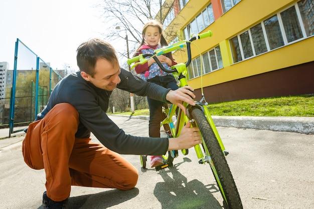 父は娘が自転車に乗るのを手伝いました。路上で自転車に乗る。健康的なライフスタイルのコンセプト
