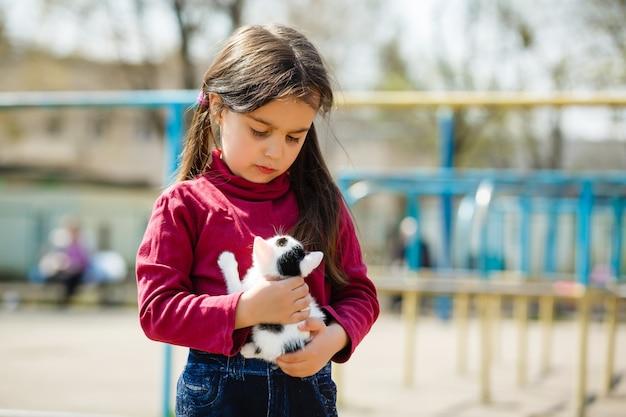小さな子猫、自然に猫と遊ぶ少女と若い子少女の屋外のポートレート