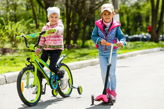 幸せなガールフレンドは幸せに笑ってけん引にスクーターと自転車に乗る