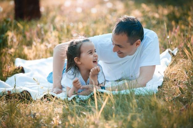 若い父親と娘の緑の芝生の上に横たわる